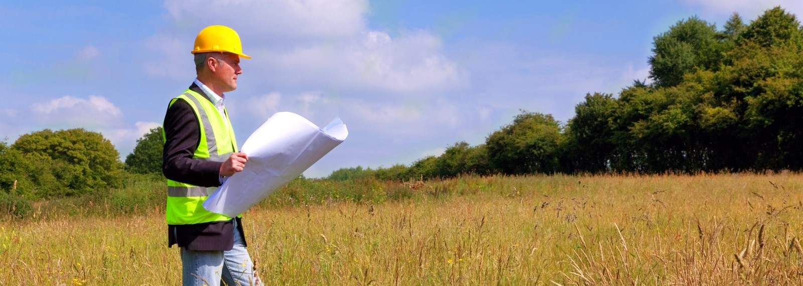 man reading planning document in a field