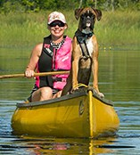 A Woman and her Dog in a Canoe in a Lake