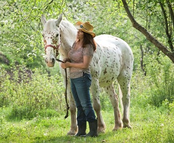 woman and horse in orchard