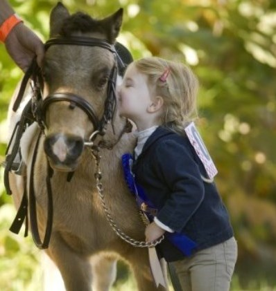 little girl giving her pony a kiss