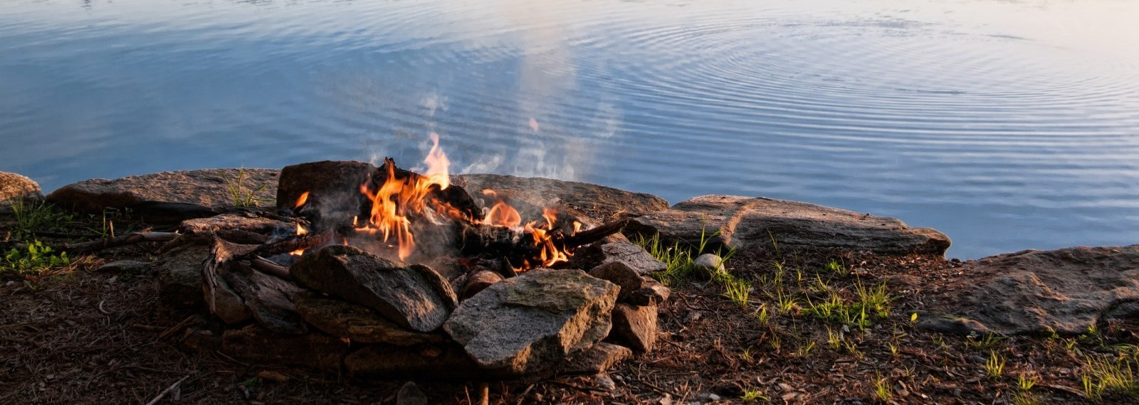 Fire-burning-in-fire-pit-on-lakeside
