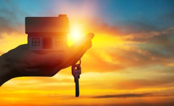 hand holding a miniature house in a sunset