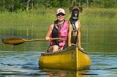 a woman and her dog in a boat on the lake