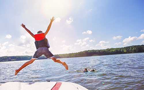 boy jumping into water off dock