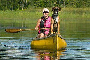 A woman and her dog in a canoe