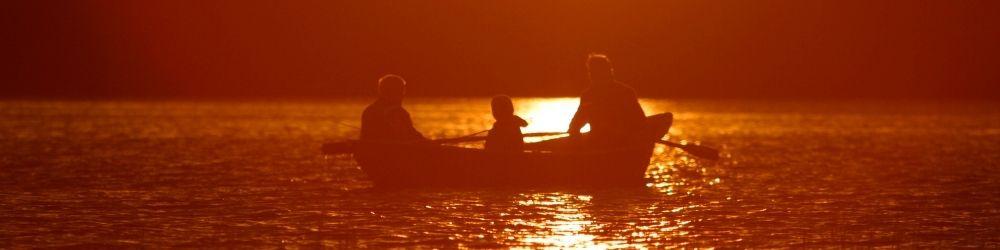family in canoe at sunset