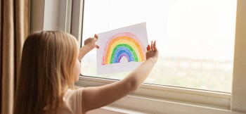 Child holds rainbow drawing up to window