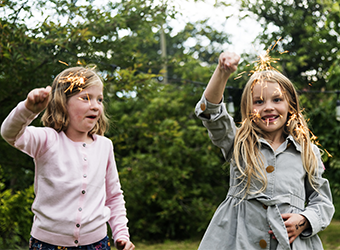 Two little girls playing with sparklers