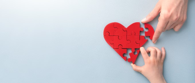 children's hand and adult's hand piece together a heart shaped puzzle