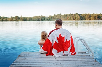 father and his kid sitting at the end of a dock with canadian flag draped over his back