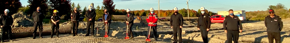 Firefighters and officials standing on the construction site for the new station