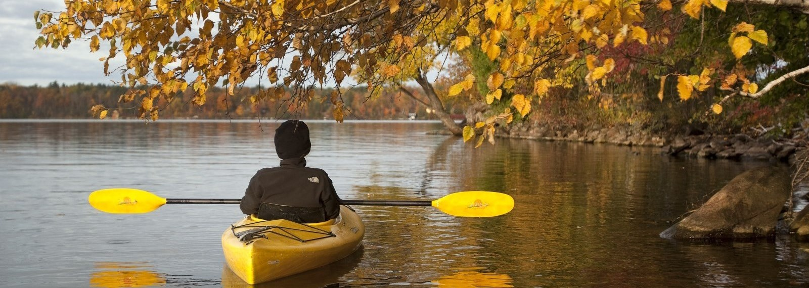 person in a canoe on the lake in the fall