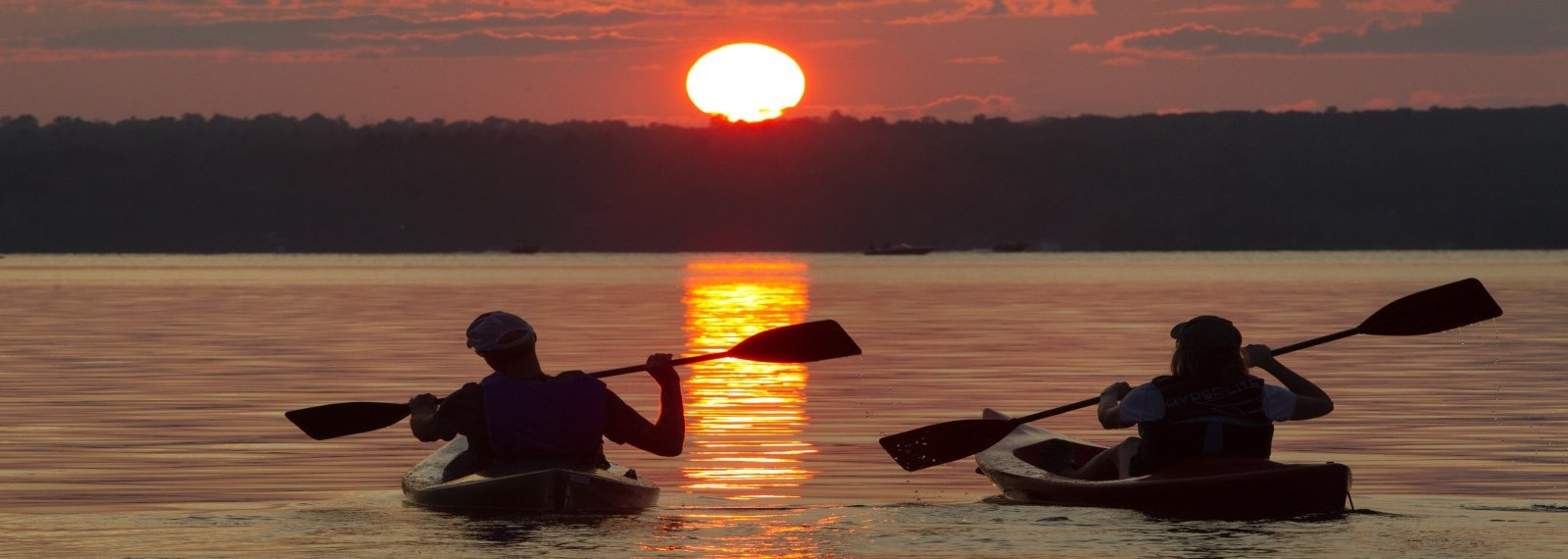 people on the lake during a sunset in their canoes