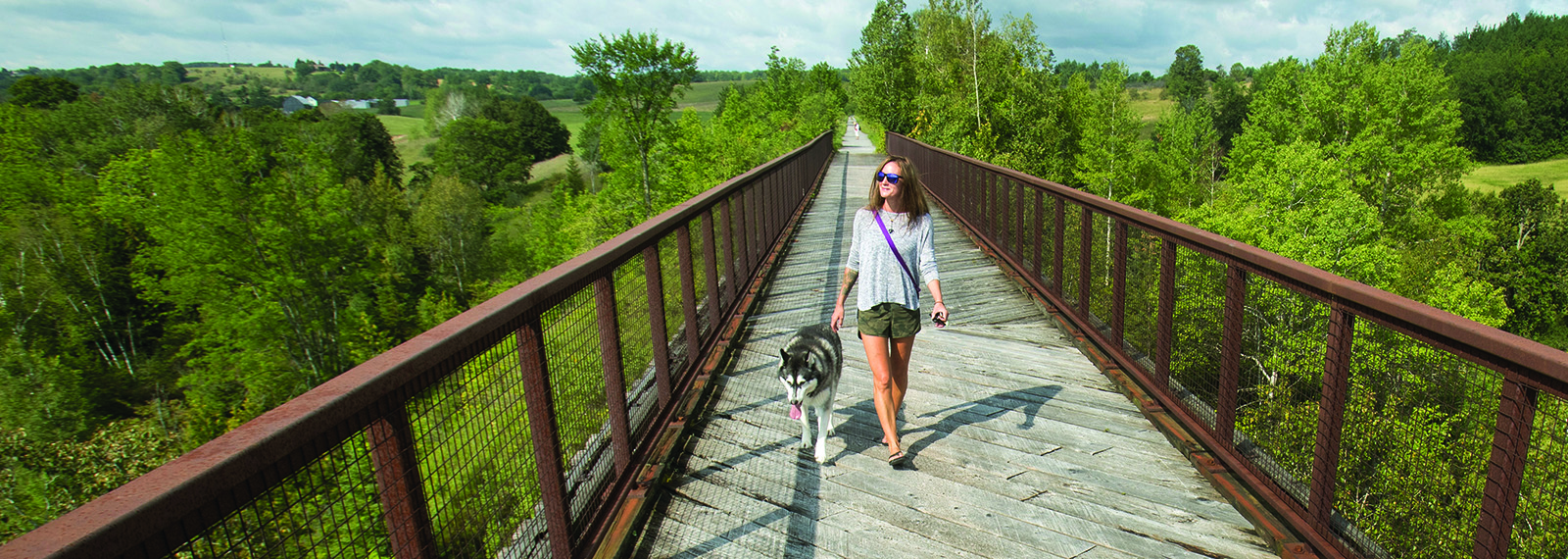 woman walking on bridge with dog