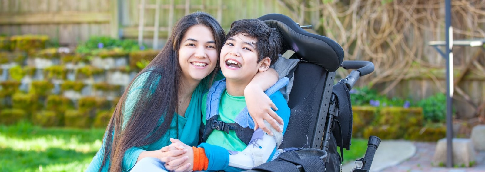 Woman and boy in wheelchair hugging