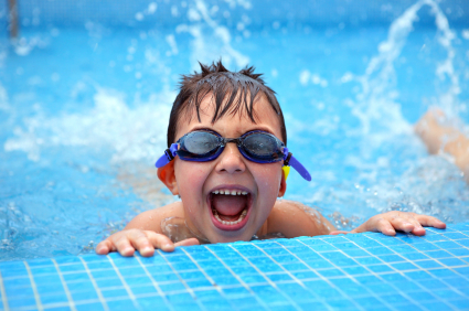 child in swimming pool with goggles