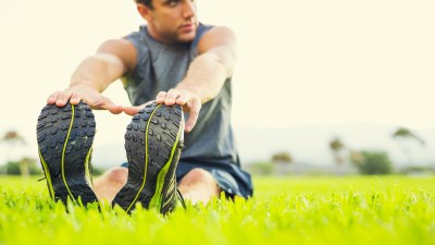 man stretching in grass
