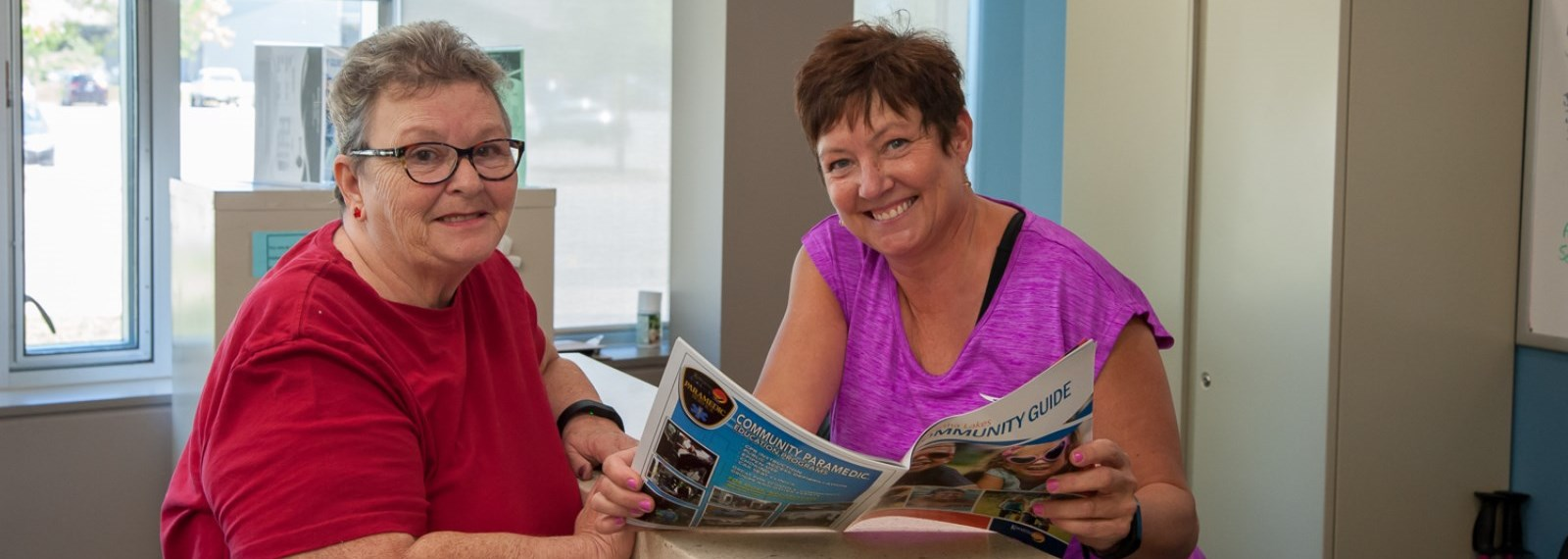Two women reading the Community Guide magazine