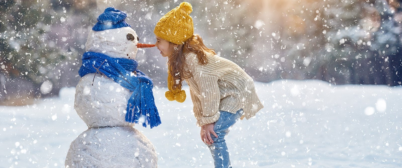 Girl looks at snowman while exploring winter in the Kawartha Lakes